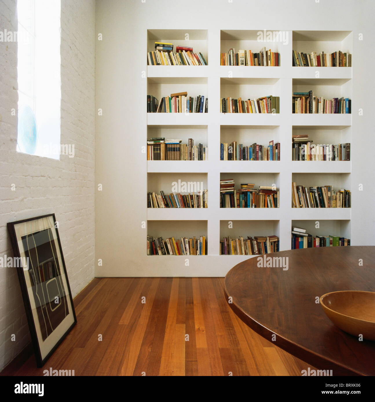 White recessed bookshelves in modern white dining room with wooden flooring - Stock Image