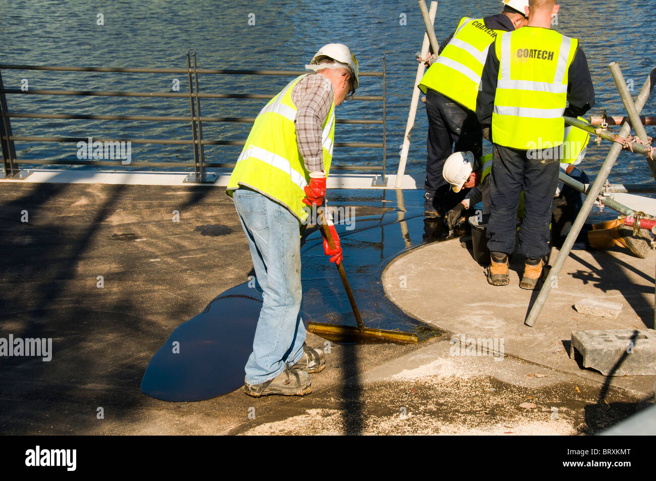 Workmen applying a resin bonded gravel surface on a new footbridge approach walkway at Salford Quays, Manchester, - Stock Image