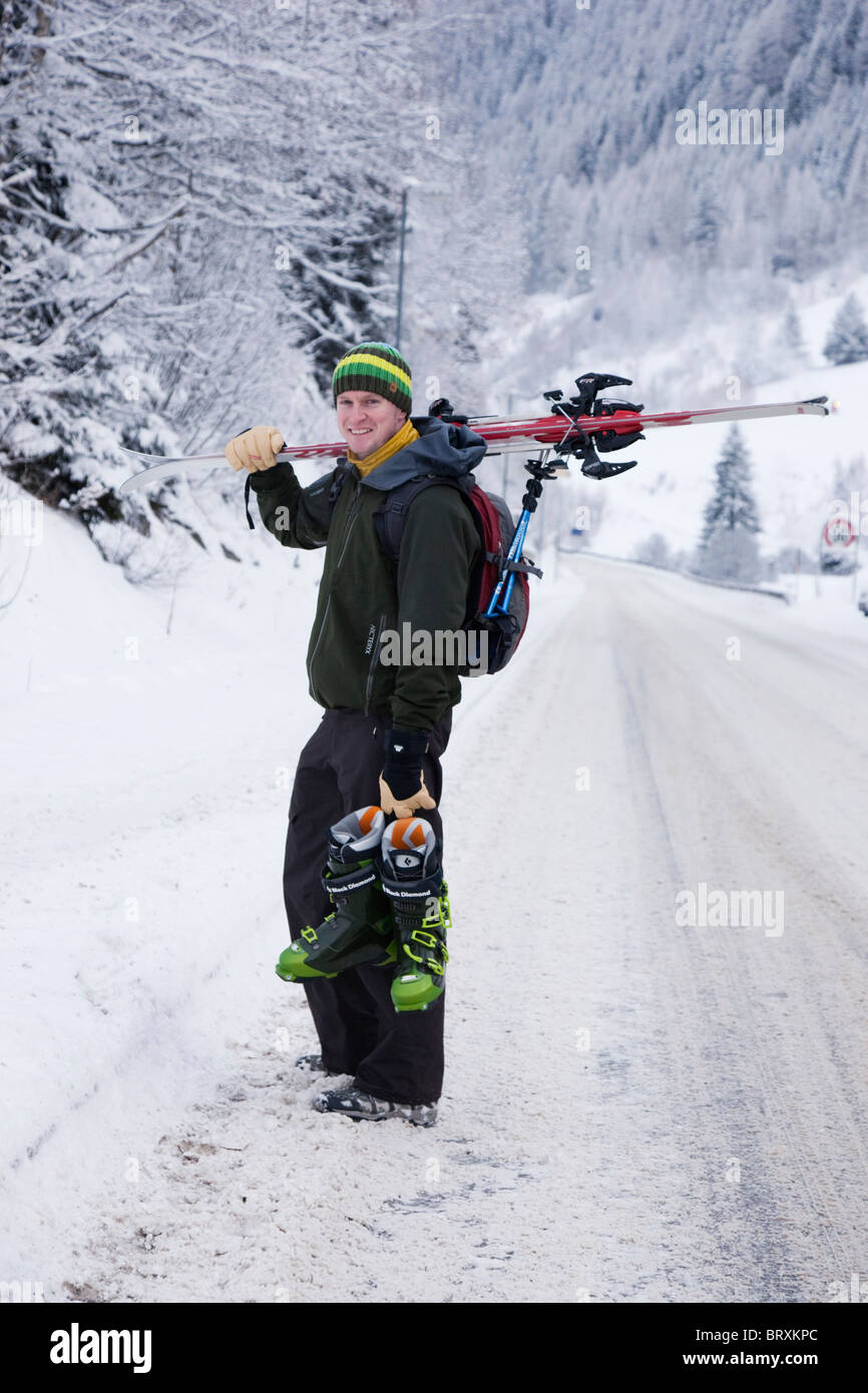 St Anton am Arlberg, Tyrol, Austria. Skier carrying ski boots with skis over his shoulder on snow covered Alpine Stock Photo