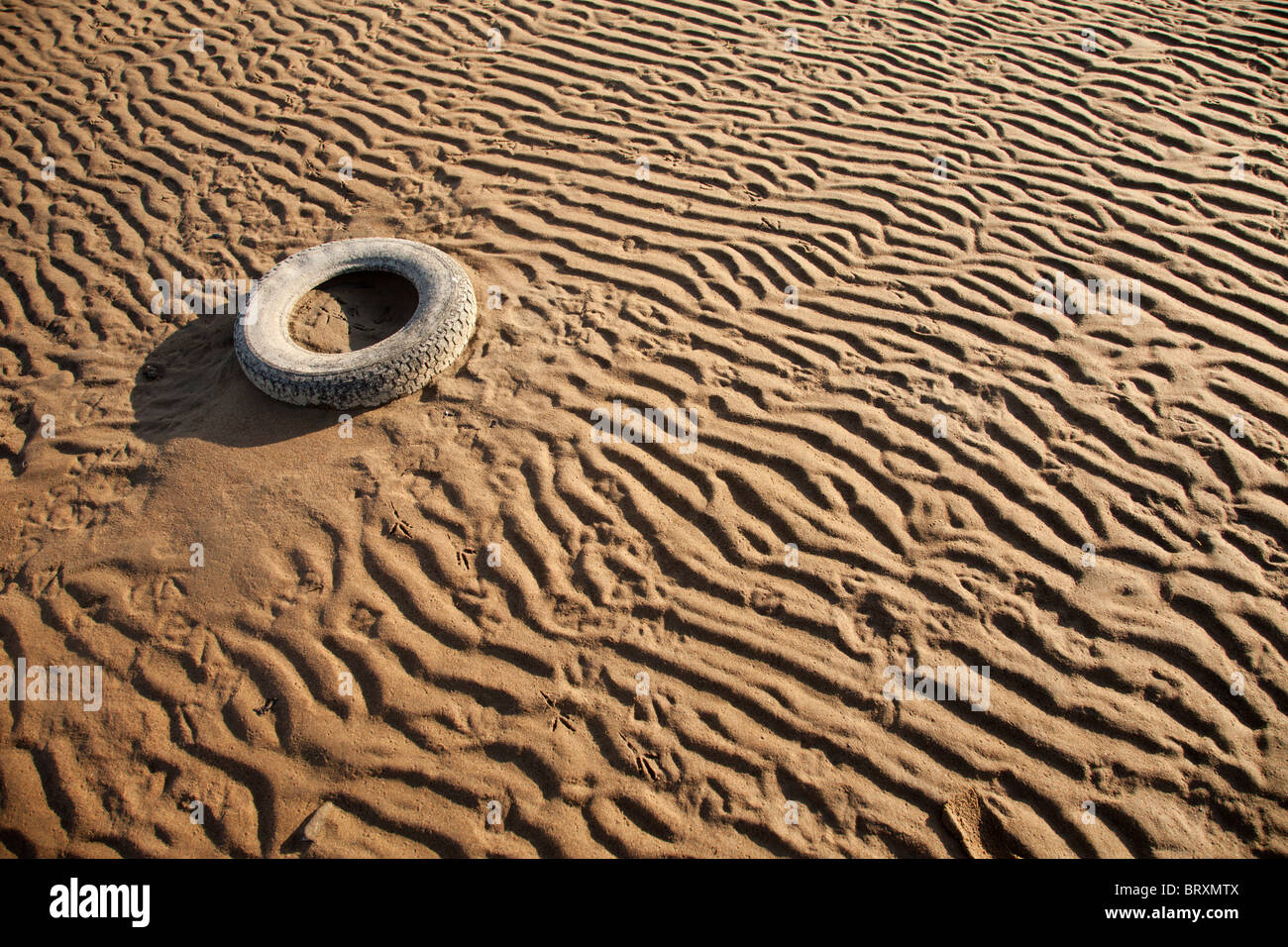 Discarded car tyre at sand beach - Stock Image