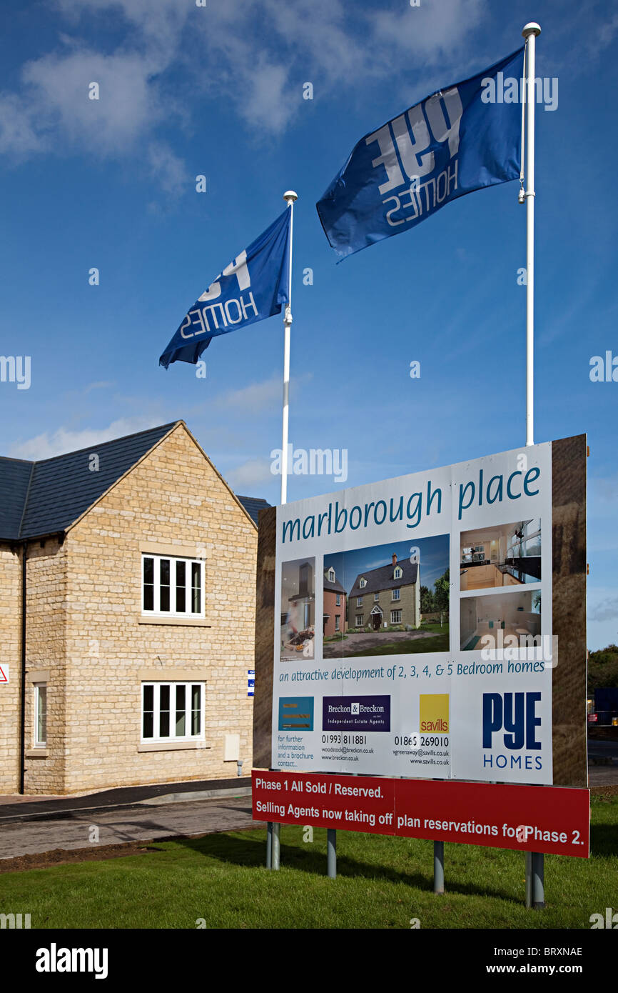Sign advertising new build houses in local stone on new estate Woodstock Oxfordshire England UK - Stock Image