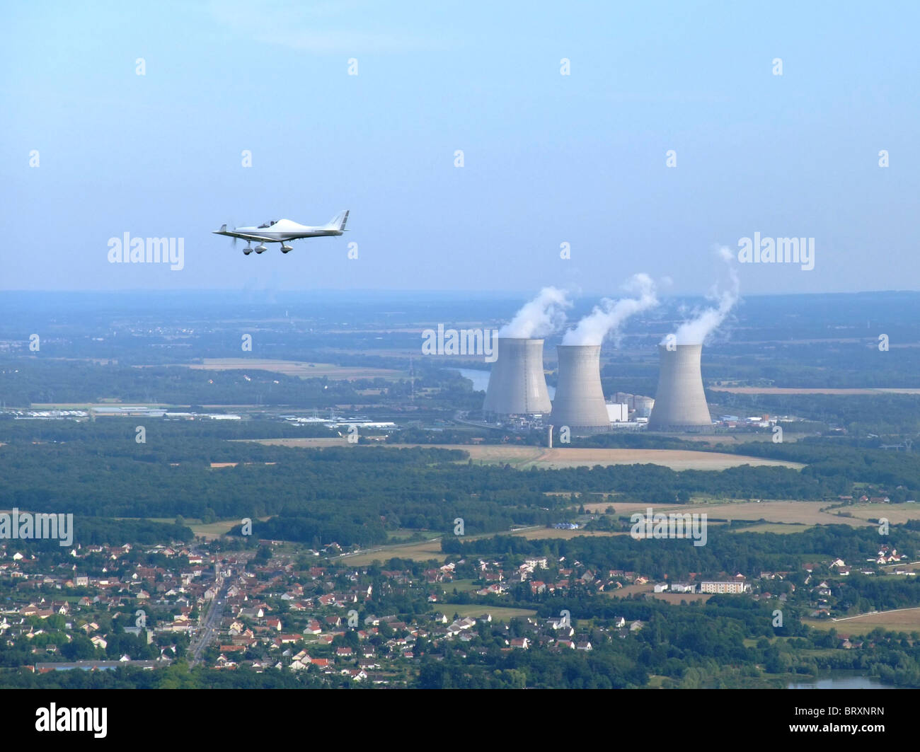Private plane flying close to the EDF nuclear powerplants of Dampierre en Burly, Loiret, Centre region, France - Stock Image