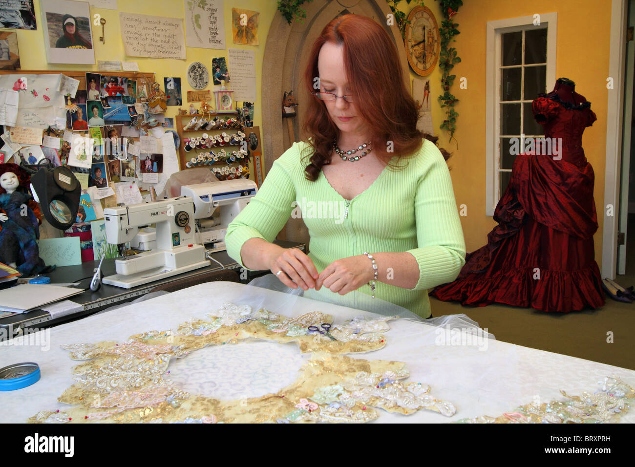 Seamstress sewing in seamstress shop with gowns and materials - Stock Image