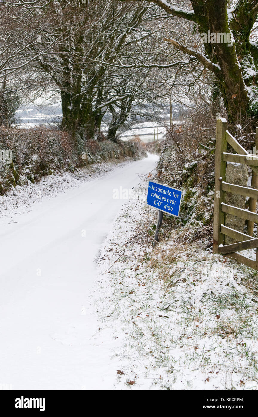 Narrow lane in snow with Unsuitable for vehicles over 6'0' wide sign, Dartmoor, Devon UK - Stock Image