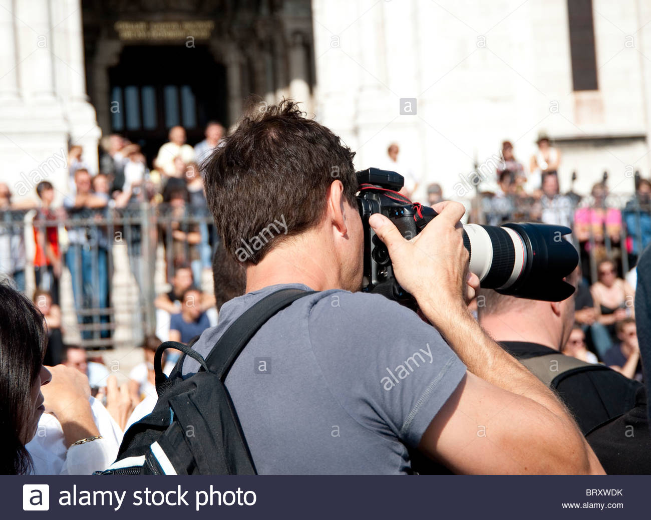 Professional photographer using a telephoto zoom - Stock Image