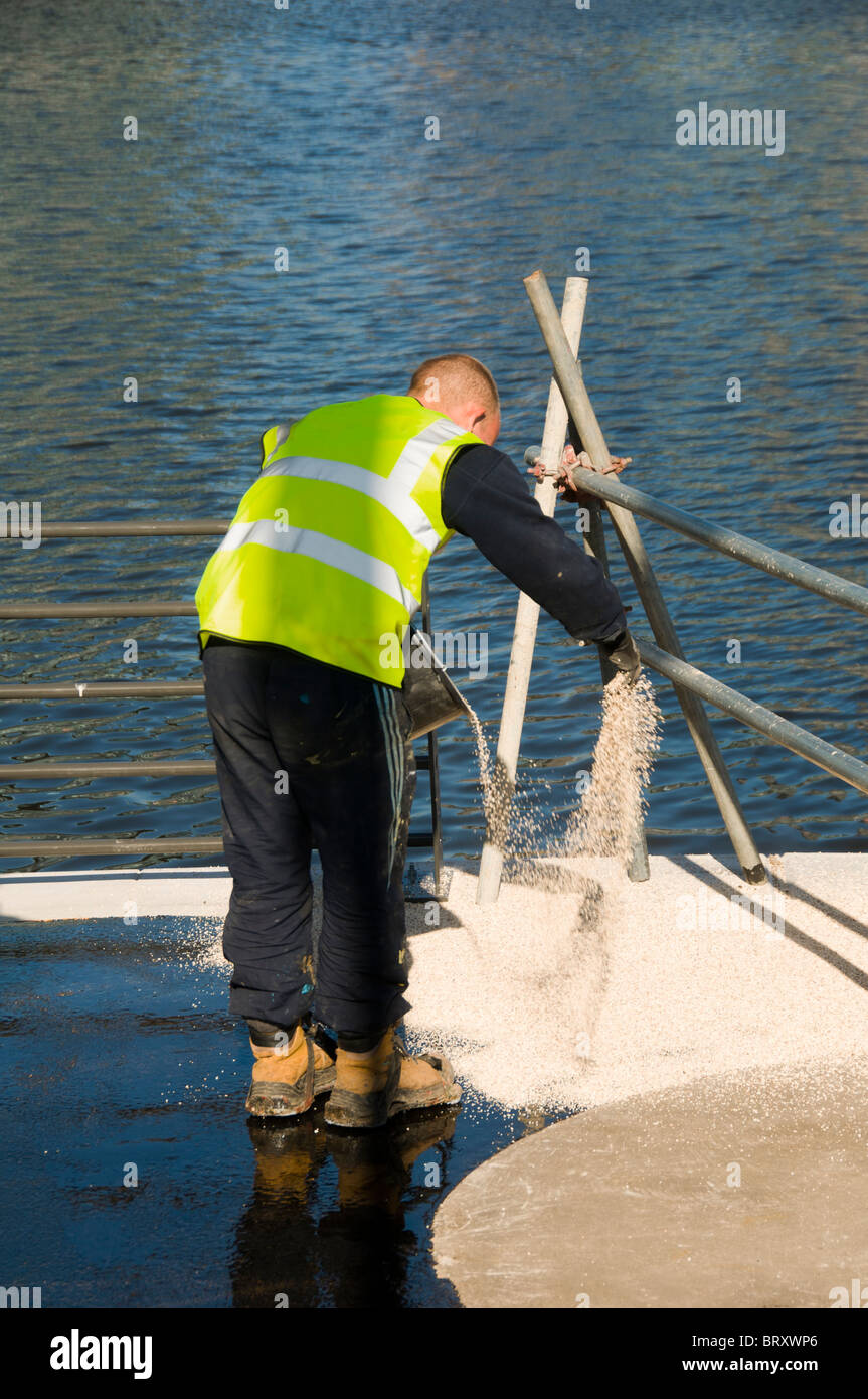 Workman applying a resin bonded gravel surface on a new footbridge approach walkway at Salford Quays, Manchester, - Stock Image