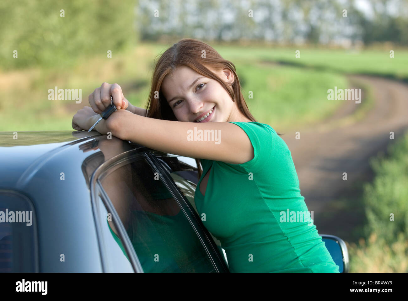 Young woman leaning pn car on country road - Stock Image