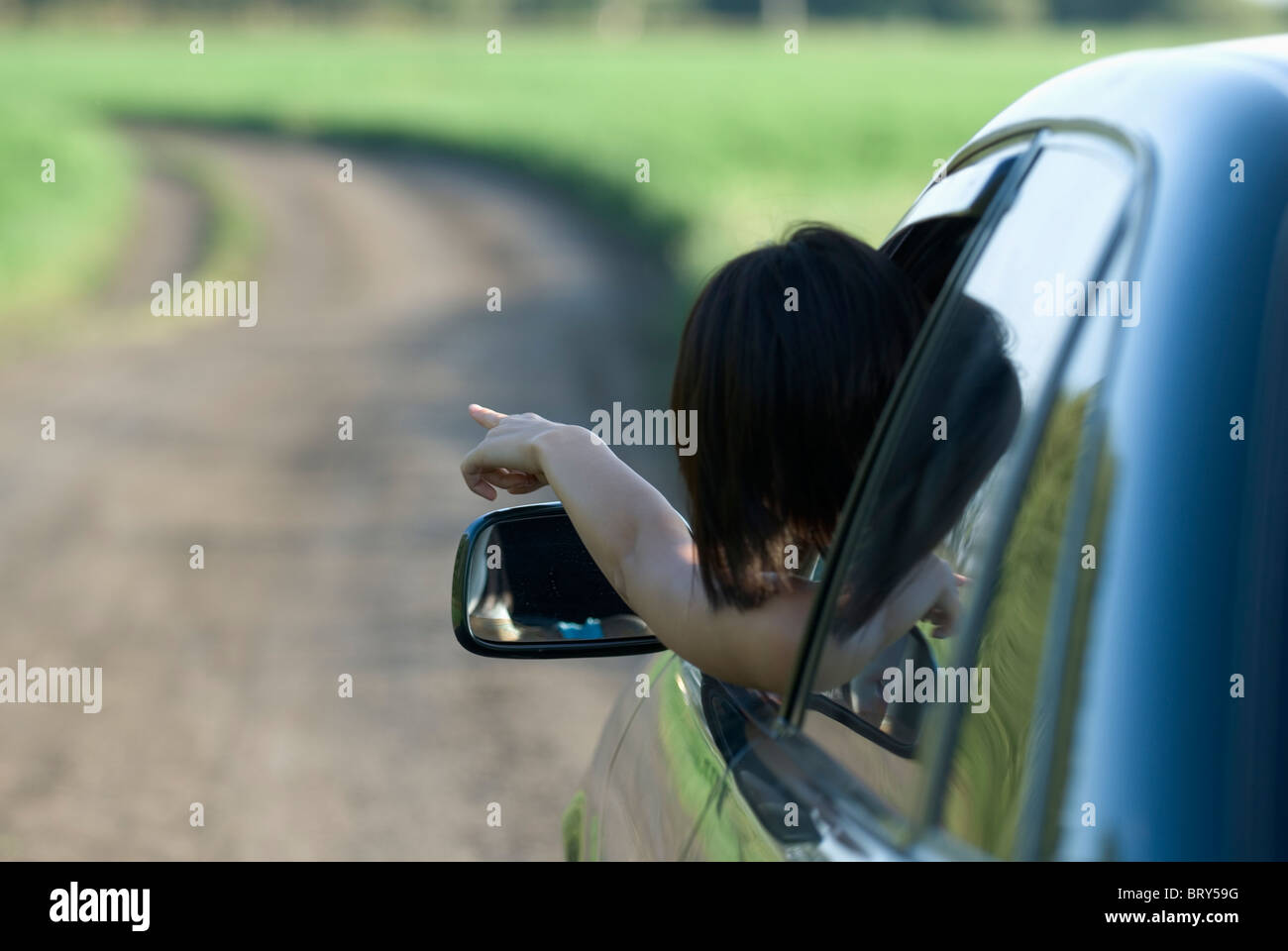 Woman leaning outside from car window and pointing - Stock Image