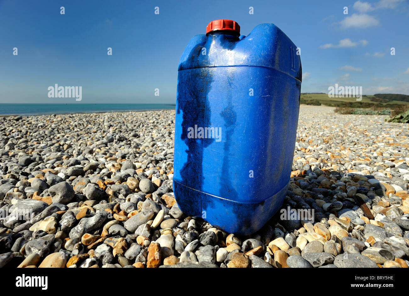 A plastic container of oil leaking and polluting a remote pebble beach - Stock Image