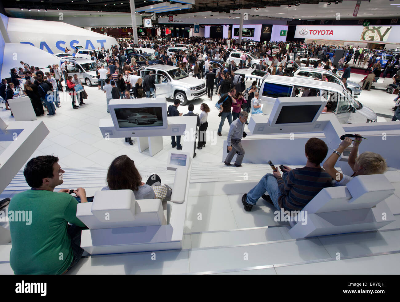 Visitors using 3D television  and view of busy hall at Paris Motor Show 2010 - Stock Image