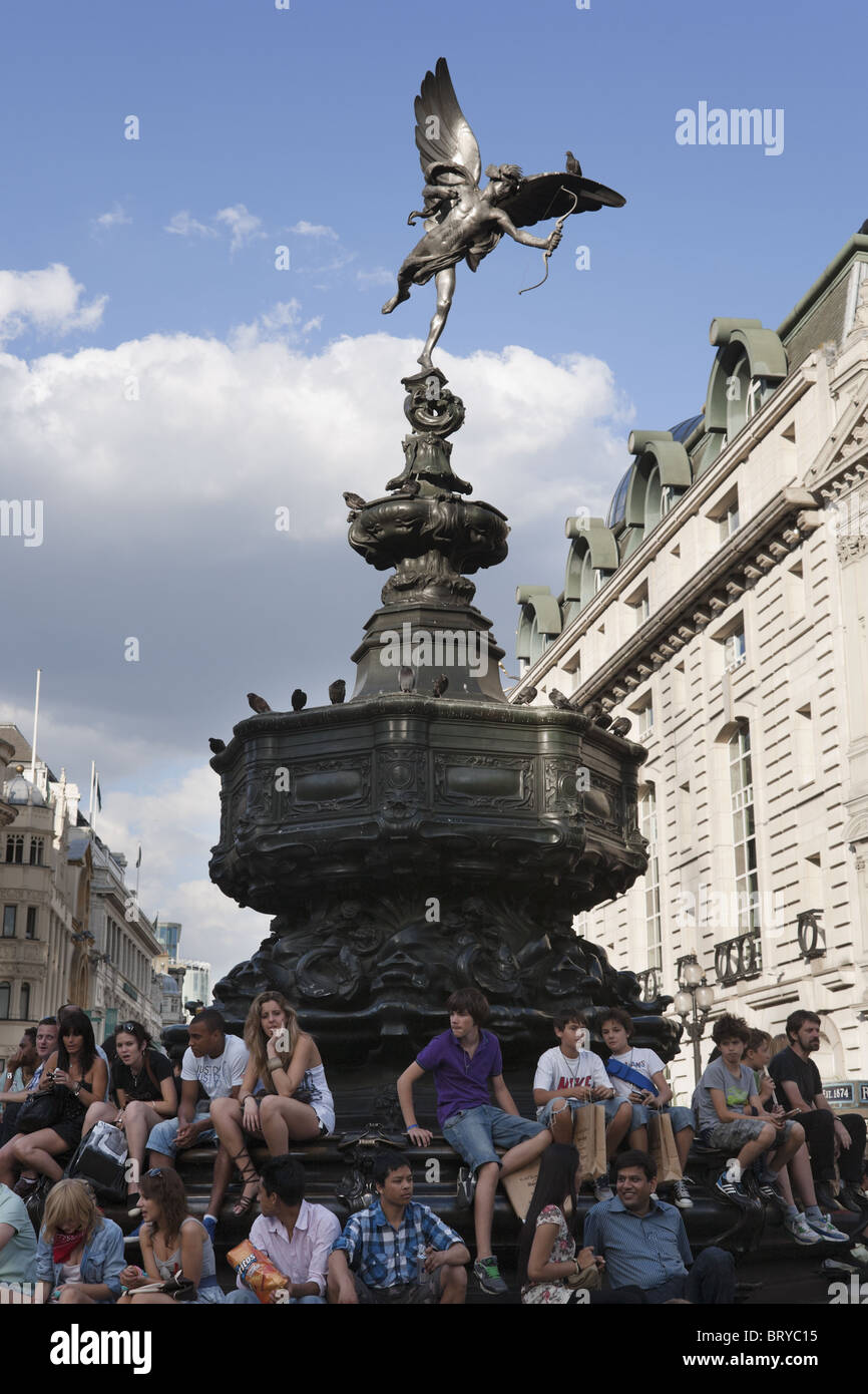 Young people sitting beneath Eros statue at Piccadilly Circus, summer, London, UK - Stock Image