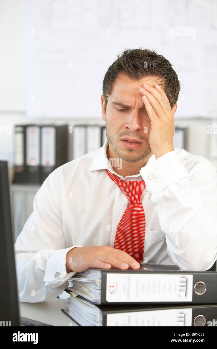 Exhausted man in the office - Stock Image