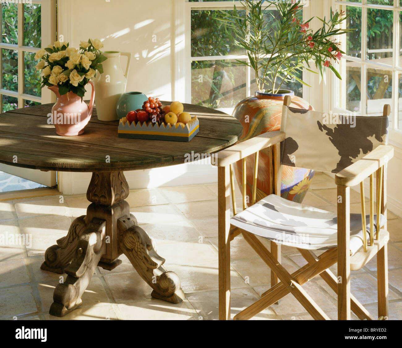 Close Up Of Circular Antique Table With Animal Print Directoru0027s Chair In  Sunny Dining Room