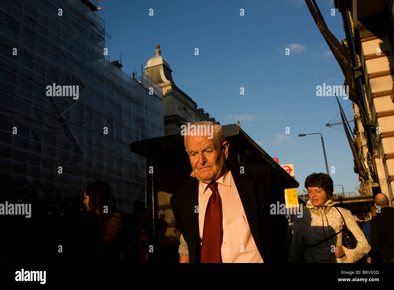 Elderly man walks slowly along Piccadilly in late afternoon sunshine. - Stock Image