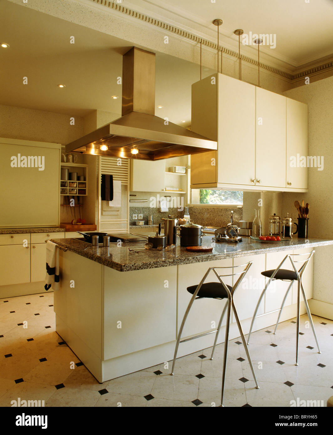 Stools at breakfast bar on peninsular unit with extractor beside ...