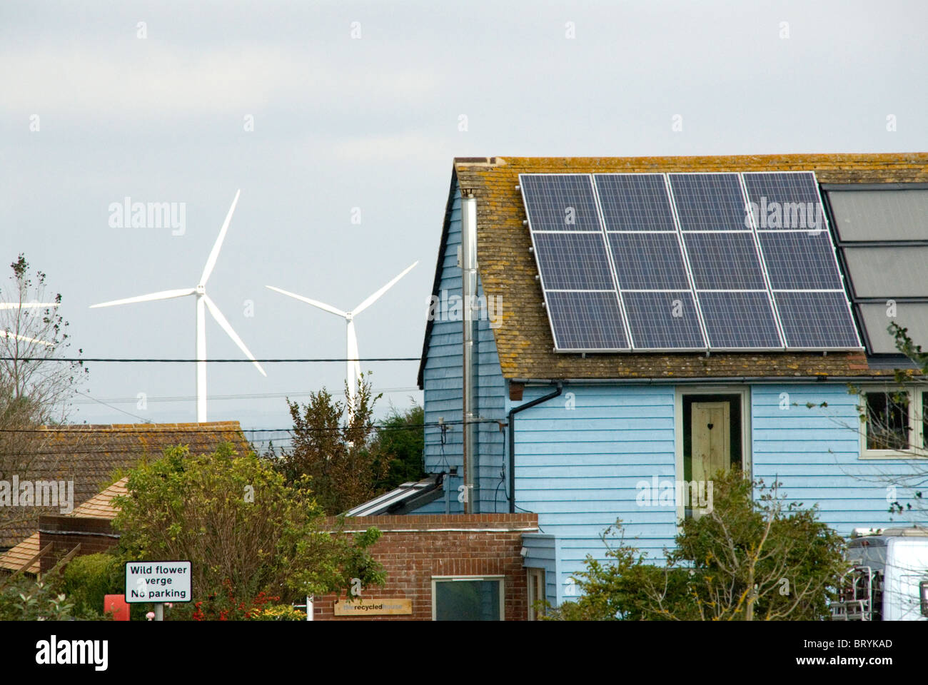 Wind turbines behind a house with solar panels The Recycled House Camber Rye east Sussex - Stock Image