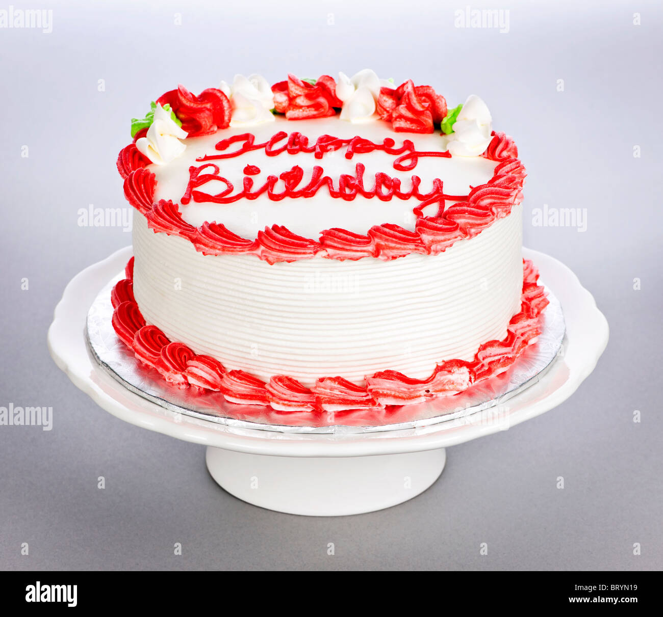 Sensational Birthday Cake With White And Red Icing On Plate Stock Photo Funny Birthday Cards Online Elaedamsfinfo