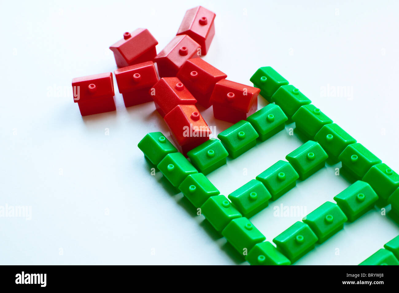 Property Ladder - Trading Up.  Monopoly green and red houses. - Stock Image