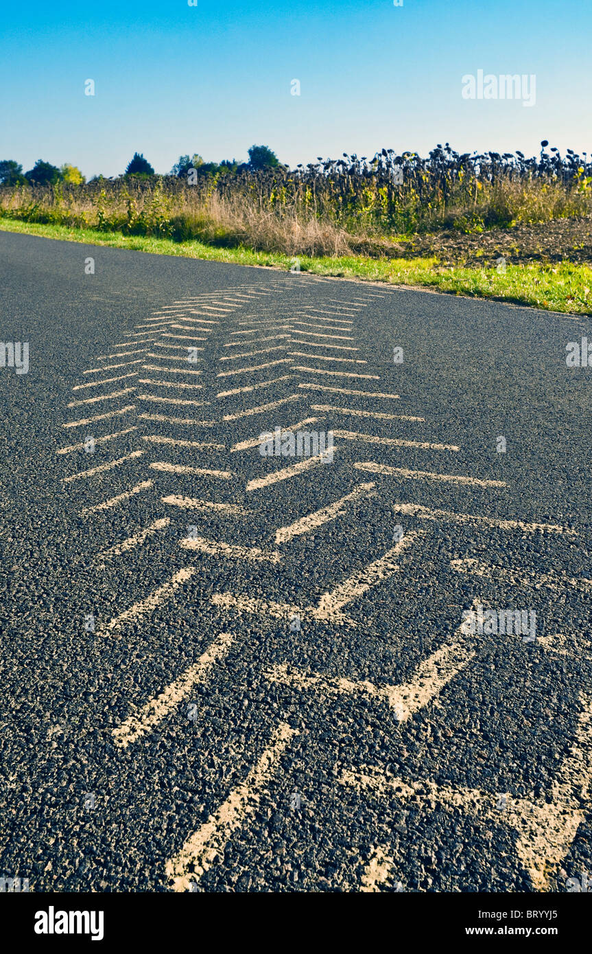 Tractor muddy tyre tracks on road surface - France. - Stock Image