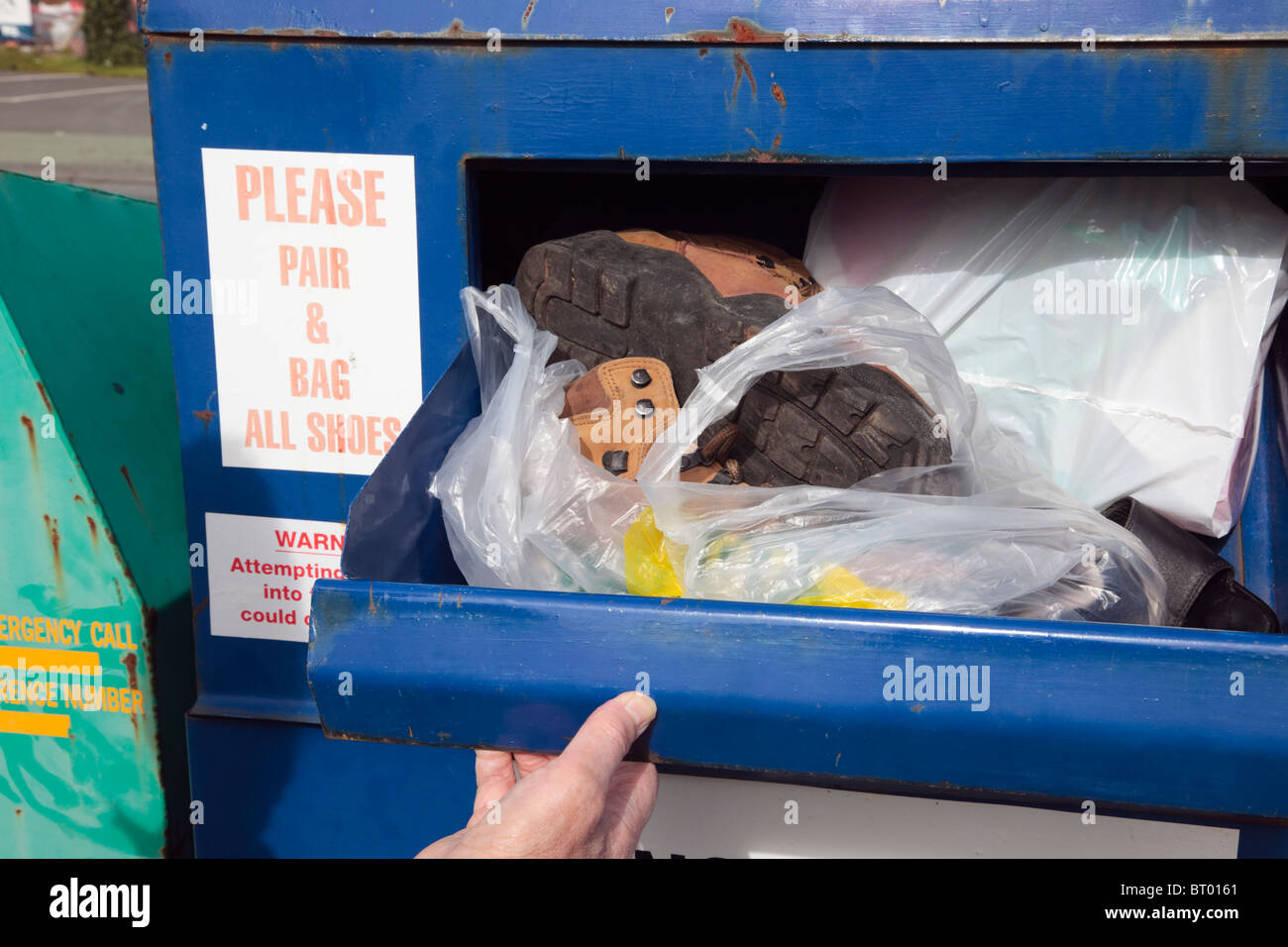 Person putting bagged old thrown out shoes into a recycling bin. UK, Britain. - Stock Image