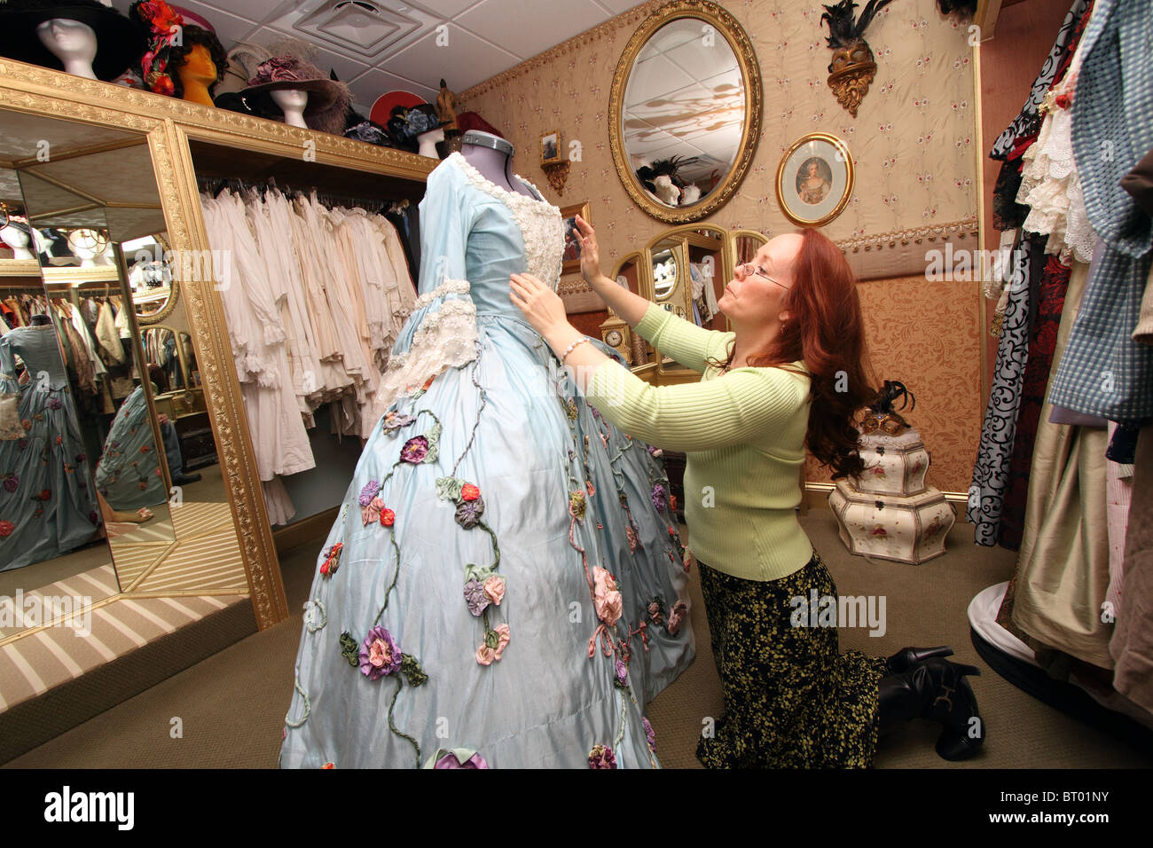 Seamstress adjusting 18th century silk gown costume for Carnival, with period costumes in seamstress wardrobe shop - Stock Image