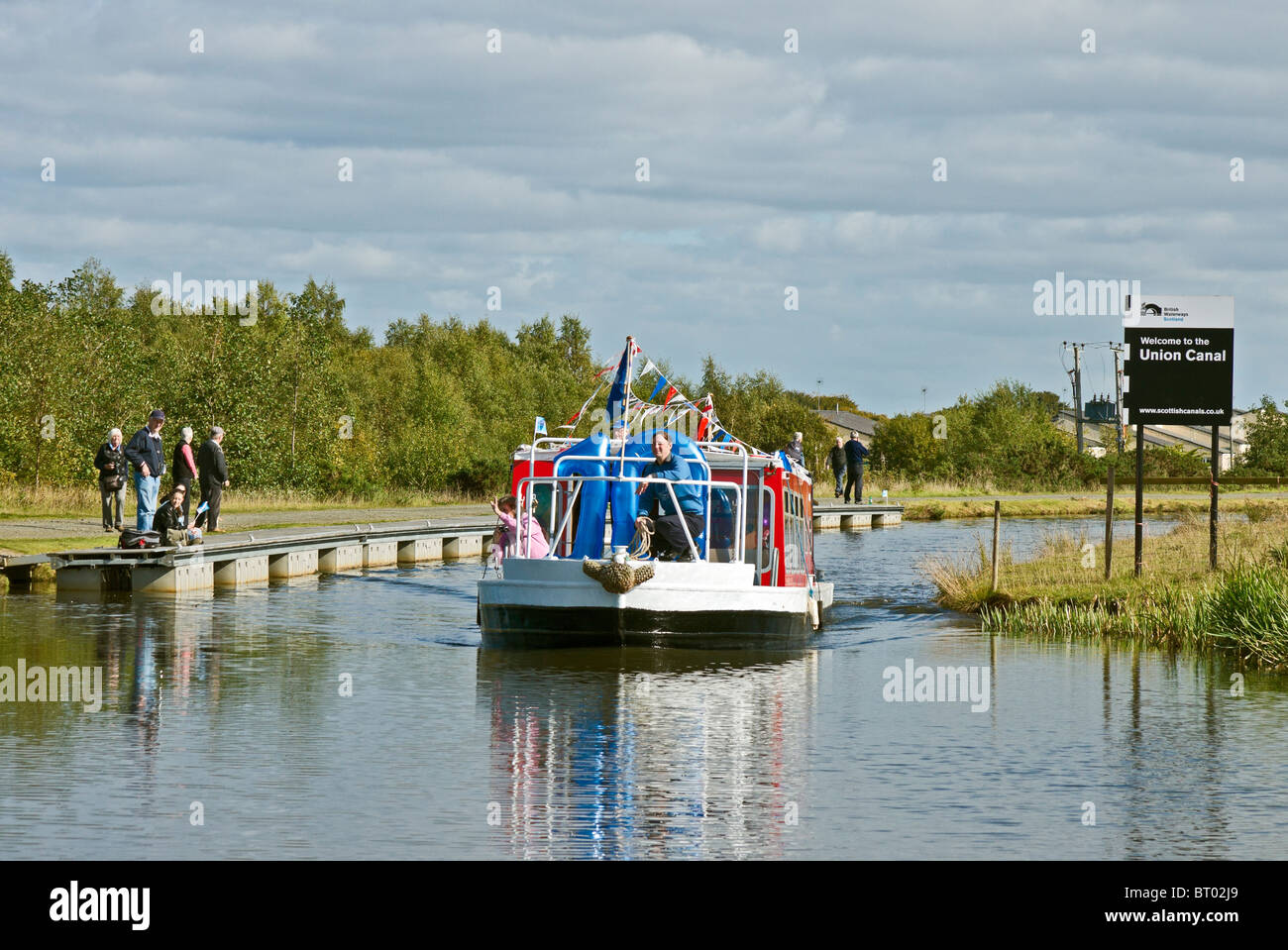 Canal boat arriving at the locks at the Union Canal near the junction with the Forth & Clyde Canal at Falkirk - Stock Image