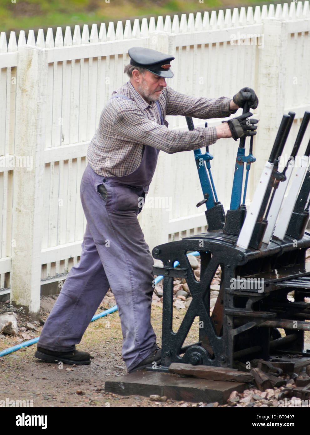 Signalman pulling levers for the historic steam train Number 828 at Aviemore, Scotland. - Stock Image
