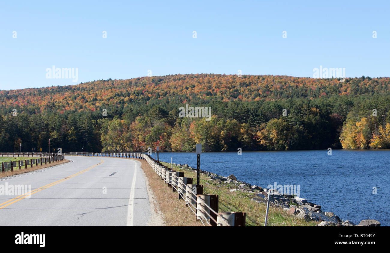 A bend in the road a lake and fall foliage. - Stock Image
