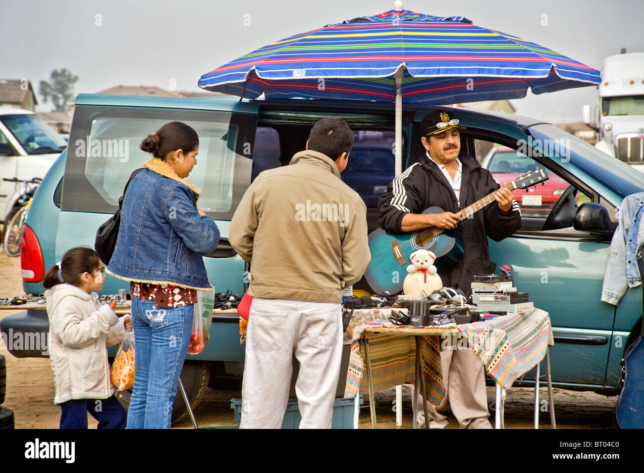A Hispanic merchant plays the guitar as customers peruse his 'flea market' items in Atwater, CA. - Stock Image