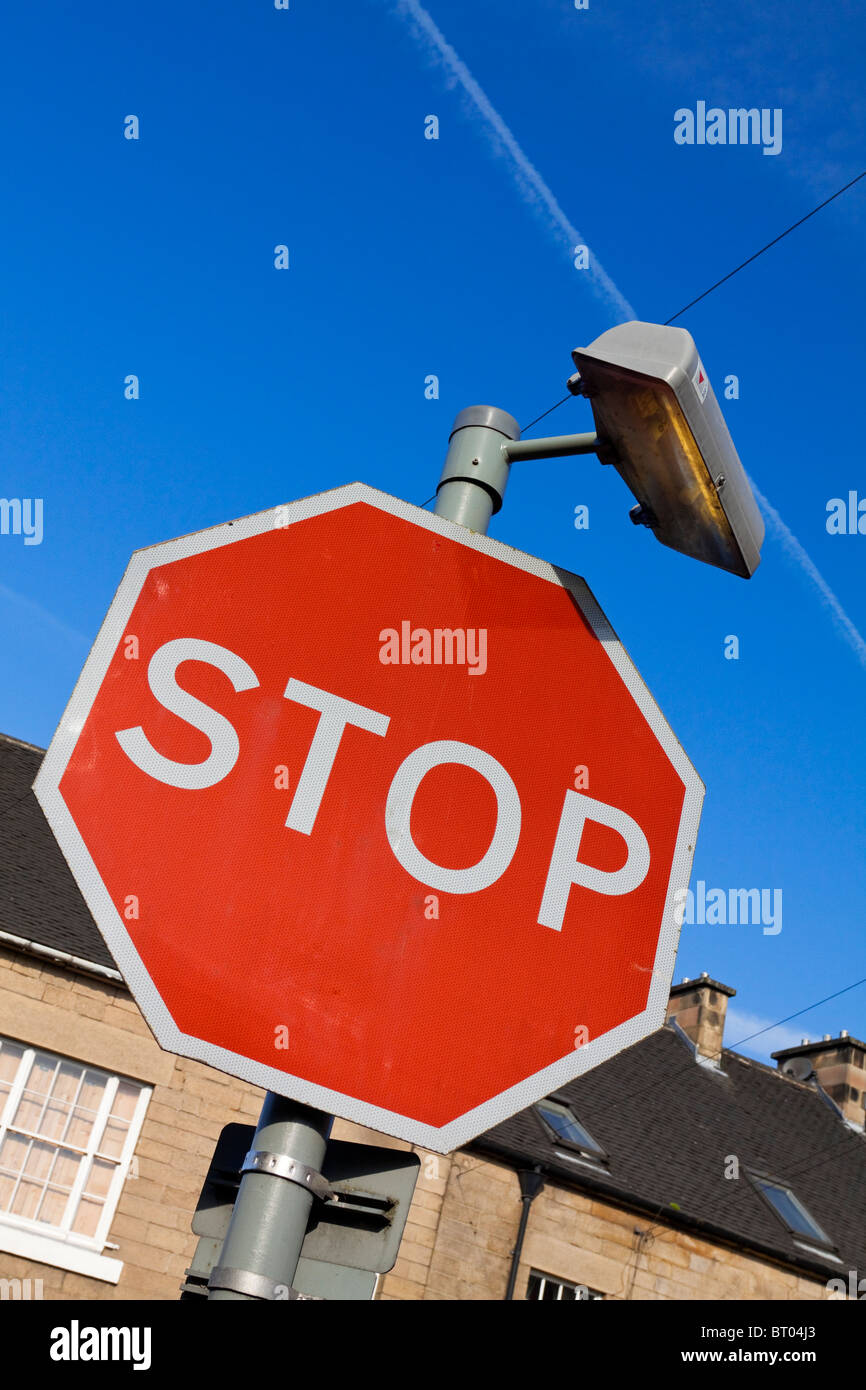 Octagonal red compulsory Stop sign used to instruct traffic to halt at a junction in the UK - Stock Image