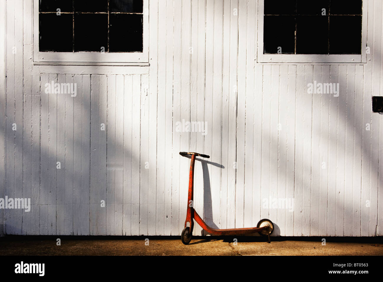 Red vintage metal scooter parked in front of while barn door - Stock Image