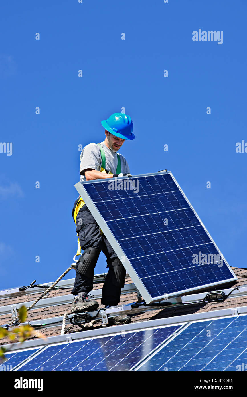 Man installing alternative energy photovoltaic solar panels on roof - Stock Image