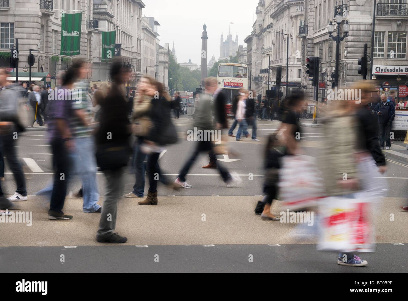 Pedestrians walk across a pedestrian crossing in Picadilly circus, London, ENgland - Stock Image
