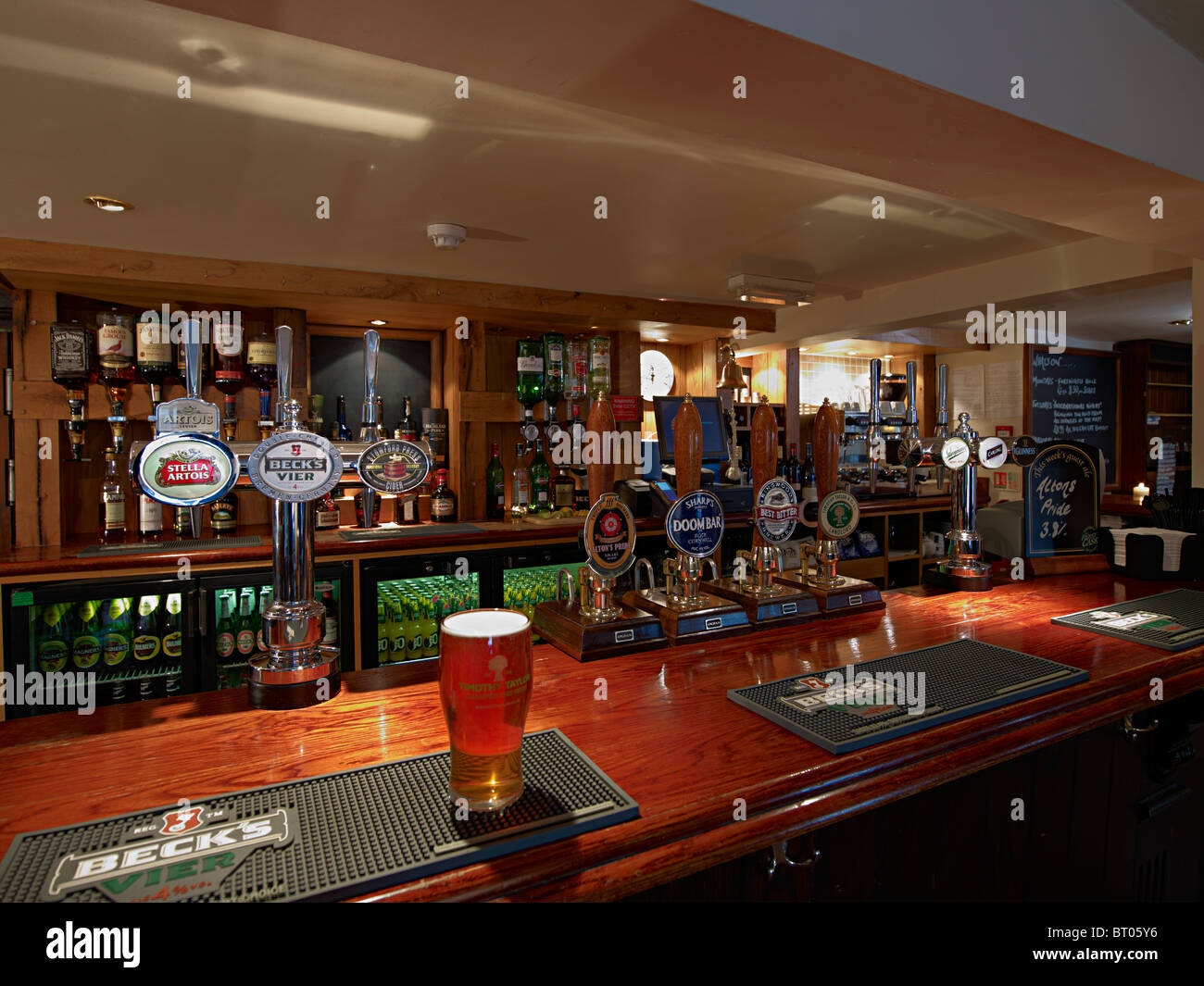 Close up of a bar in an old english pub with bar pumps and optics and a pint of beer in the foreground Stock Photo