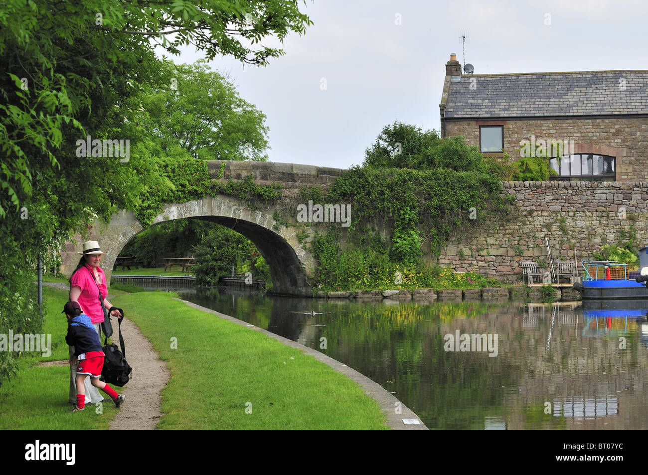 Mother son play towpath, landscape stone bridge,water refections - Stock Image