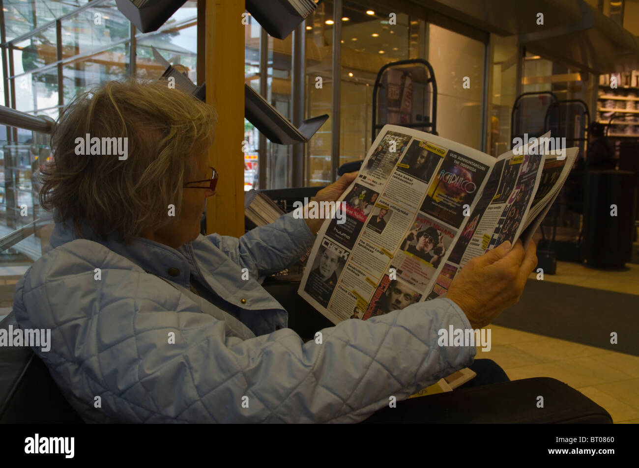 Senior woman reading ads in a free daily newspaper Helsinki Finland Europe - Stock Image