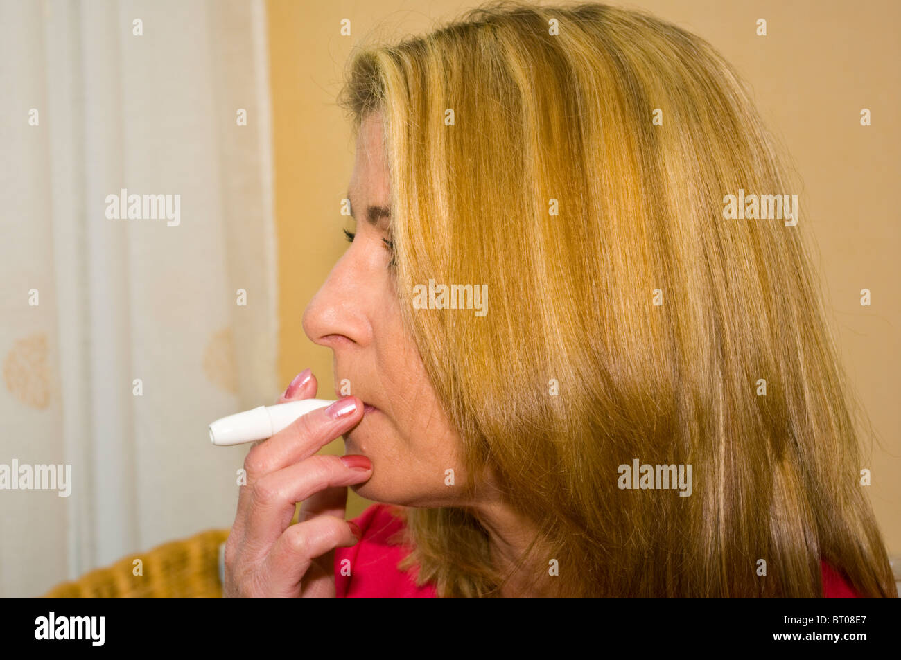 Middle Aged Woman Using A Nicotine Inhalator - Stock Image