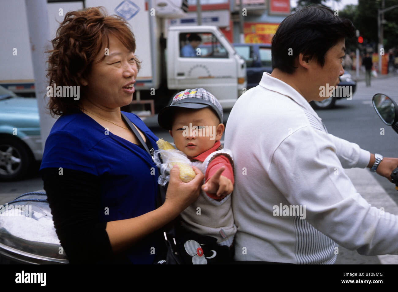 A little boy on an electric cycle with his family members in Shanghai, China.  2009 - Stock Image