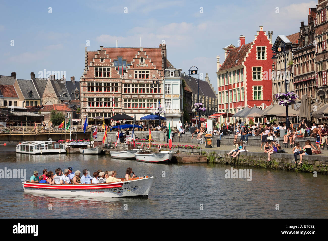Graslei Site, Ghent, East Flanders, Belgium, Tourists in sightseeing boats on River Leie with medieval Flemish Guild - Stock Image