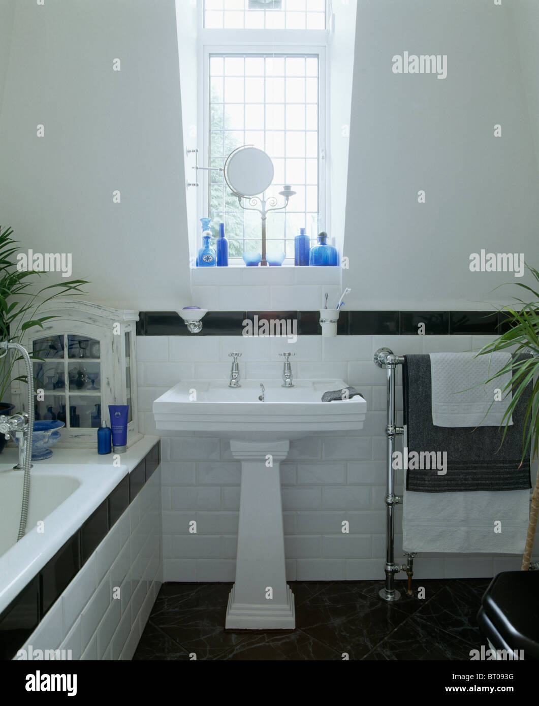 White pedestal basin in white attic bathroom with black tiled border ...
