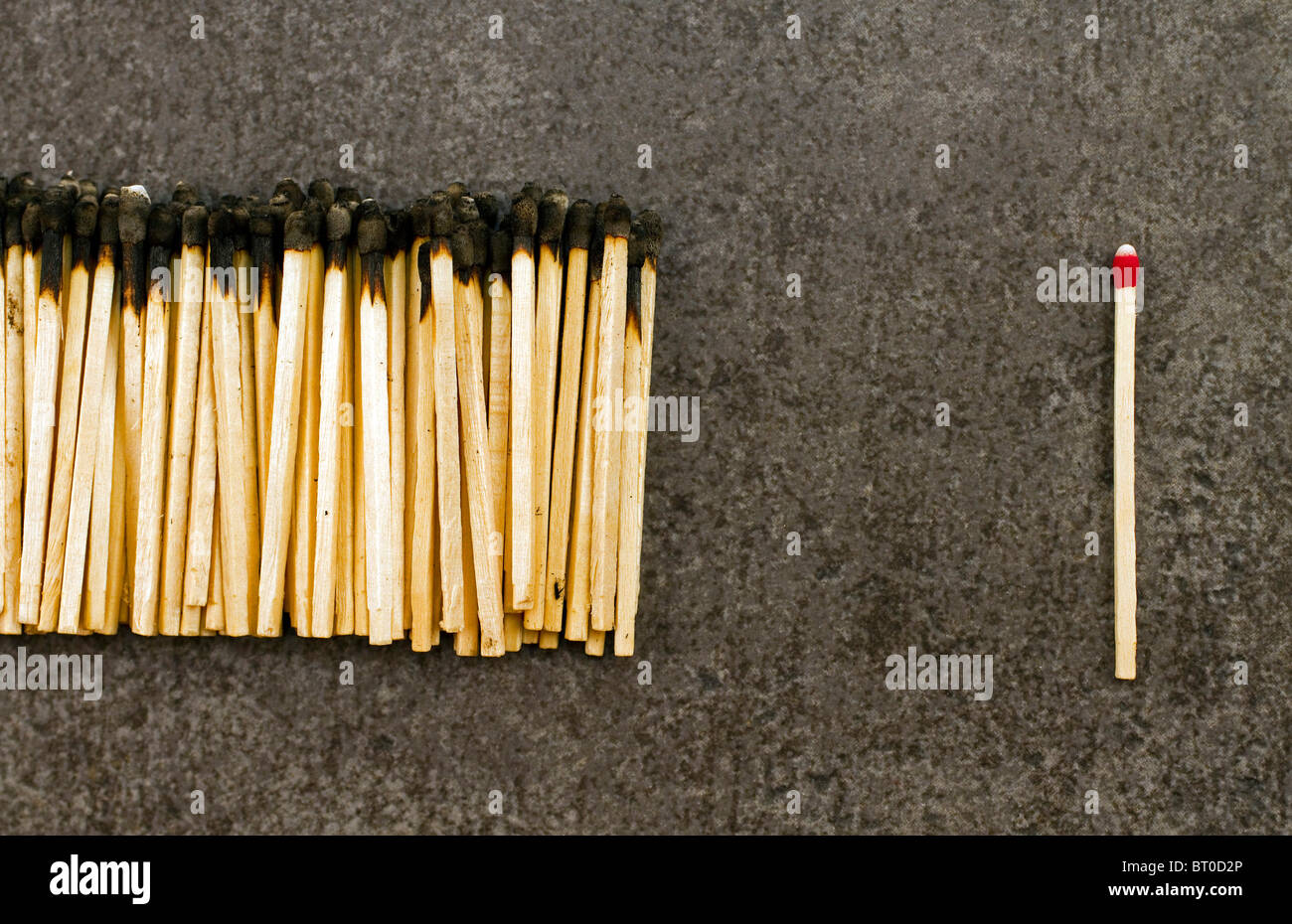 A single unused match next to a bunch of burnt ones. - Stock Image
