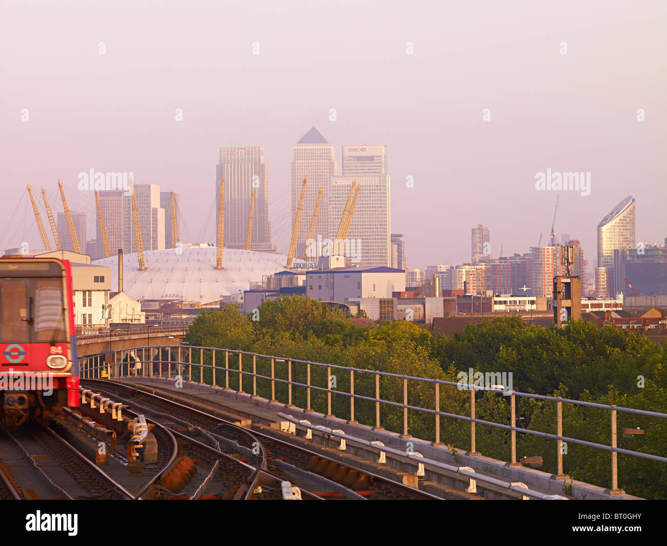 London DLR at sunrise with Docklands, Canary wharf and the Millennium Dome in the rear. - Stock Image