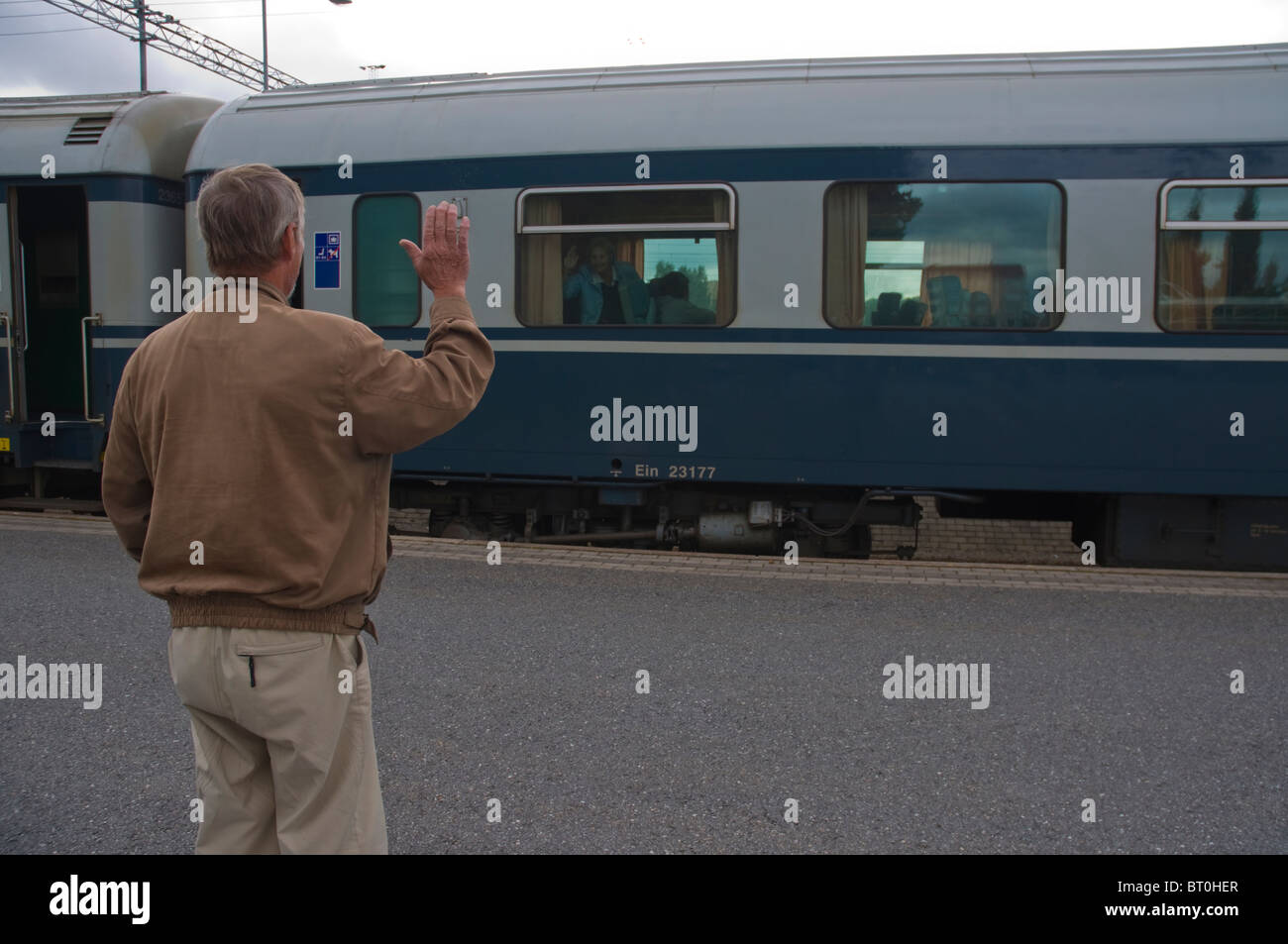 Senior waving goodbye to people on train in Finland Europe - Stock Image