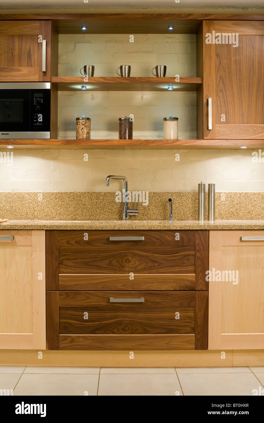 Down lit shelves above sink in fitted unit with dark wood drawers in pale wood