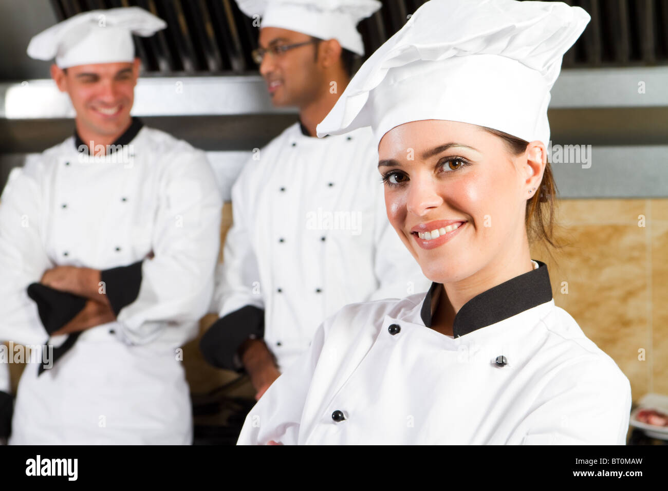 group of young beautiful professional chefs portrait in industrial kitchen Stock Photo