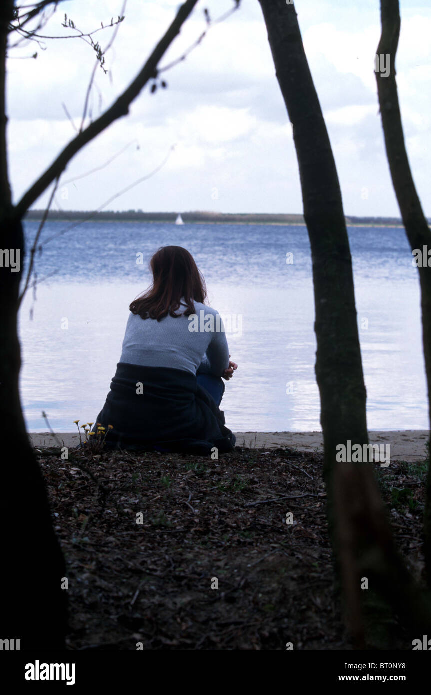 Back view young woman contemplate at shore line, - Stock Image