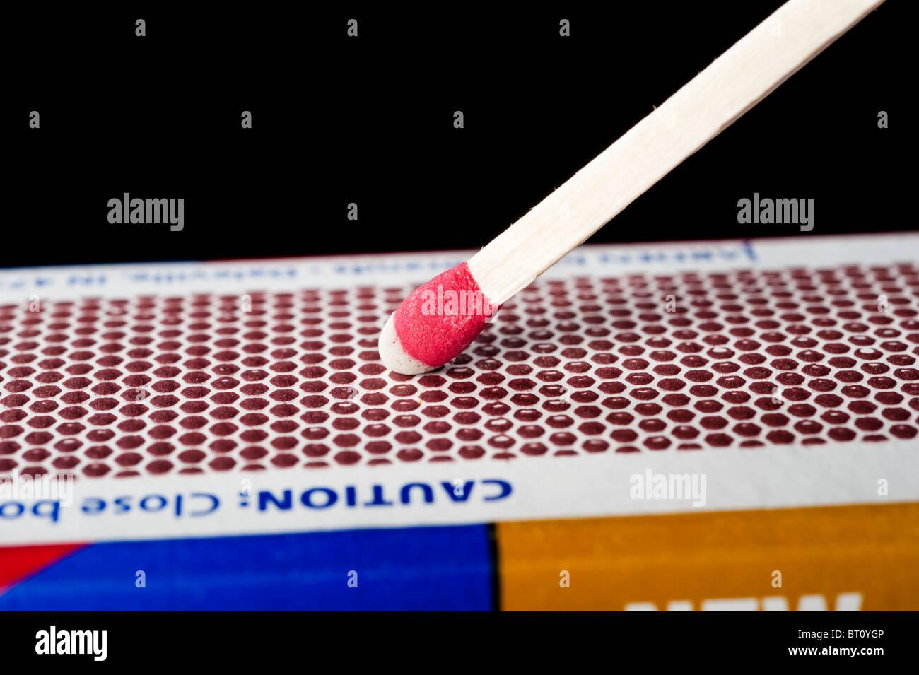 A wooden match stick on a matchbox striking surface. - Stock Image