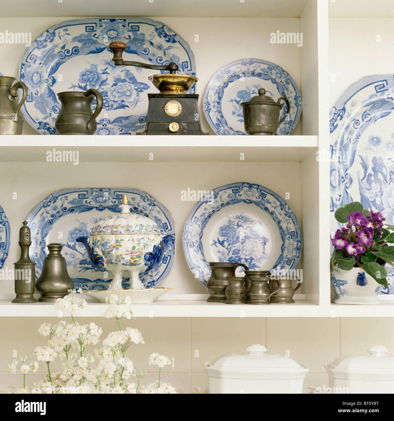 Close-up of collection of antique blue+white plates on white shelves with pewter Prinknash pottery jugs and old coffee-grinder & Close-up of collection of antique blue+white plates on white shelves ...