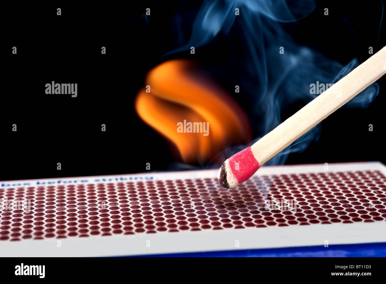A matchstick lights after it is struck against the flint surface of a match box. - Stock Image
