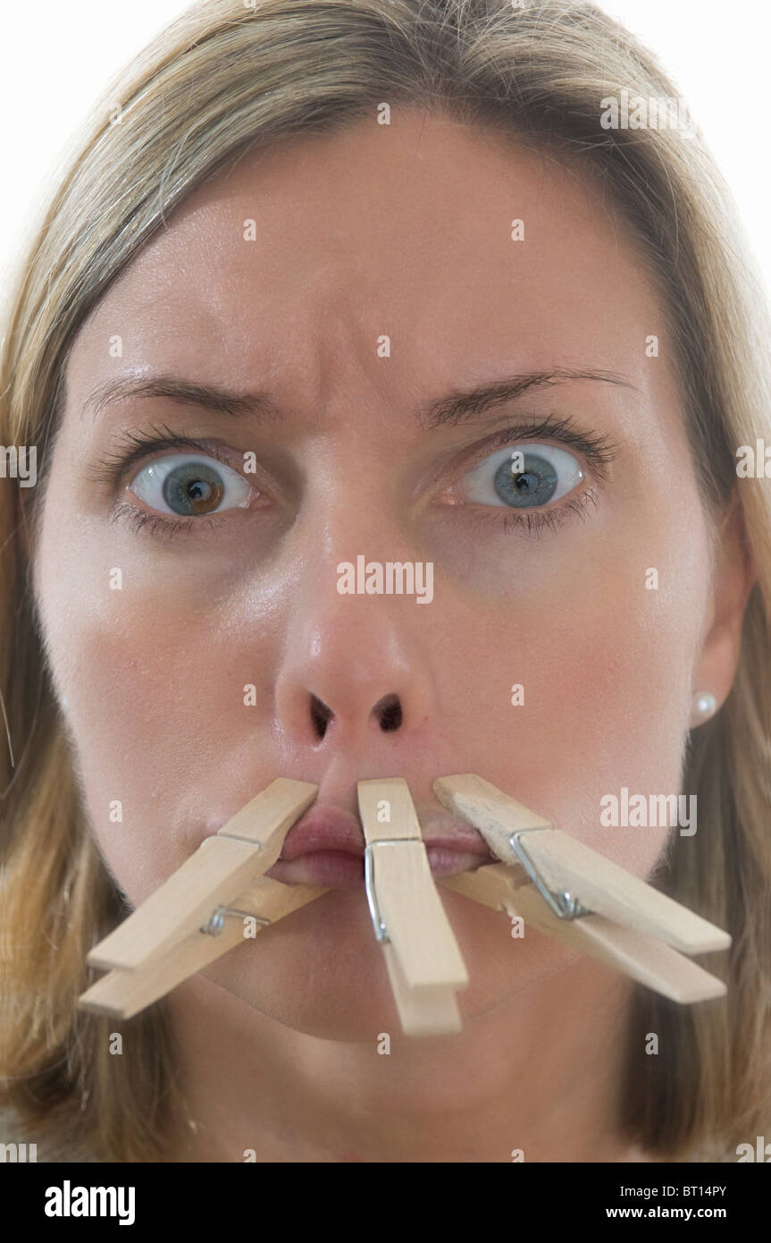 Woman with mouth pegged closed shut - Stock Image